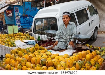RAWALPINDI, PAKISTAN - JULY 16: Unidentified Pakistani boy sells fruits at Raja Bazaar on July 16, 2011 in Rawalpindi, Pakistan. Raja Bazaar is the main shopping area in Rawalpindi. - stock photo
