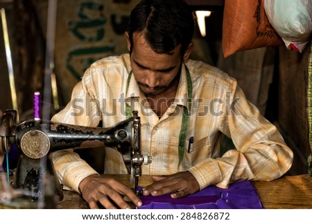 RAXAUL - NOV 7: Indian man working in his sewing workshop on Nov 7, 2013 in Raxaul, Bihar state, India. Bihar is one of the poorest states in India. The per capita income is about 300 dollars. - stock photo