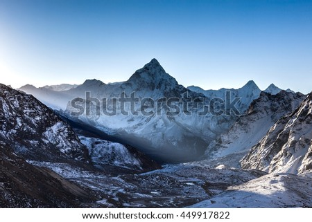 Ray of light beaming through mountains in front of Ama Dablam summit on the famous Everest Base Camp trek in Himalayas, Nepal. Beautiful mountain landscape in the beginning of a bright sunny day. - stock photo
