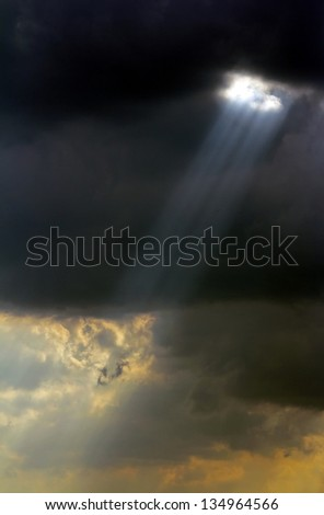 Ray of sunlight through the black clouds before the storm. - stock photo