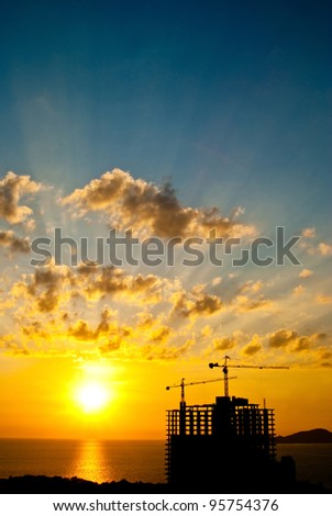 Ray on black cloud when sun set back tower crane - stock photo
