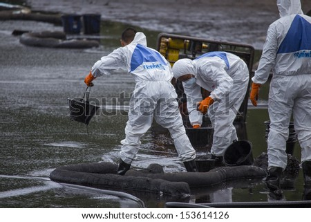 RAYONG, THAILAND - JULY 31, 2013: Workers wearing biohazard suits scoop a pail full of spilled crude oil as cleaning operations from a beach of Samet Island on July 31, 2013 in Rayong, Thailand.