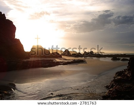 Rays of light pass through a crucifix on a rocky coastline