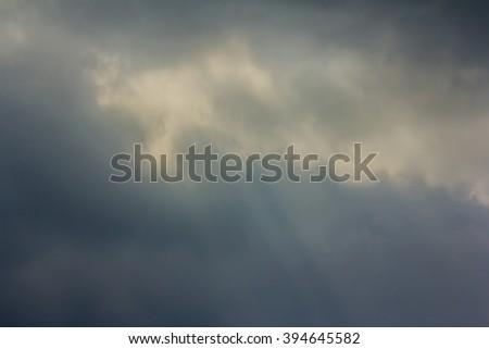 Rays of light shining through dark clouds - stock photo