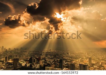 Rays of light shining through dark clouds city Bangkok, Thailand - stock photo