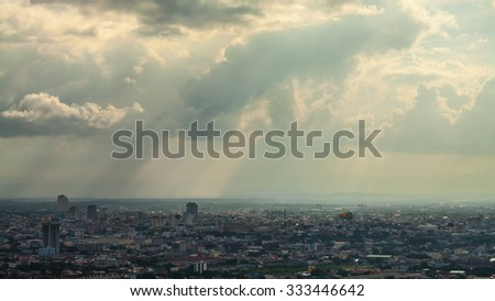 Rays of light shining through dark clouds in Thailand - stock photo