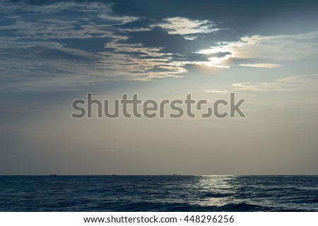 Rays of light shining through the clouds in to the sea. - stock photo