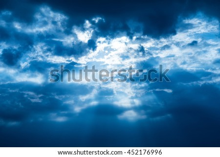 Rays of light shining through the clouds with blue filter - stock photo