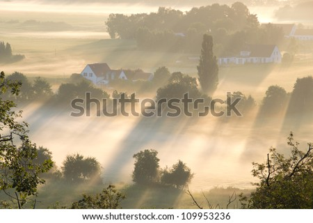 Rays of morning light illuminate fields and houses in the Netherlands on a foggy morning. - stock photo