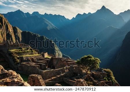 Rays of Sun light on the ruins of Machu Picchu, Peru, South America - stock photo