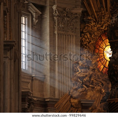 Rays of sunlight shine in the window onto the main altar of St. Peter's Basilica, in Rome, Italy. - stock photo