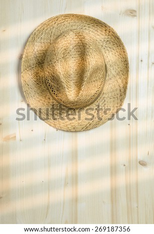 Rays of sunshine on a straw hat hanging on a wooden wall with copy space for your text - stock photo