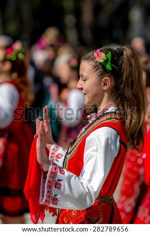 "RAZLOG, BULGARIA - APRIL 13, 2015: A beautiful Bulgarian girl dancing during the traditional folklore festival ""1000 national costumes"" - stock photo"