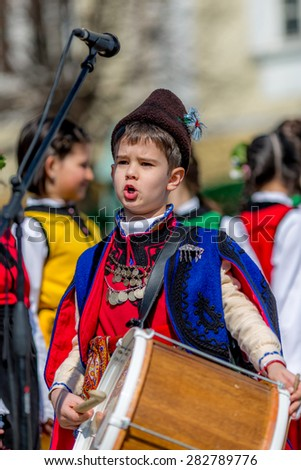 """RAZLOG, BULGARIA - APRIL 13, 2015: A small Bulgarian boy playing on drums on the stage during the traditional folklore festival """"1000 national costumes"""" - stock photo"""