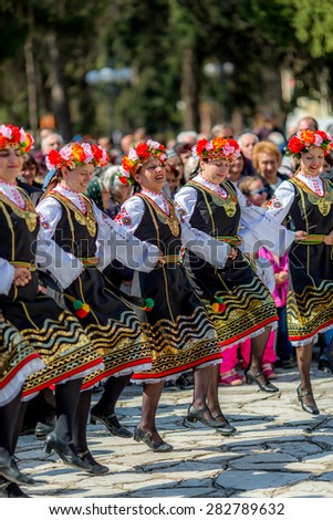 """RAZLOG, BULGARIA - APRIL 13, 2015: Female Bulgarian folklore dancers playing a round dance during the traditional folklore festival """"1000 national costumes"""" - stock photo"""