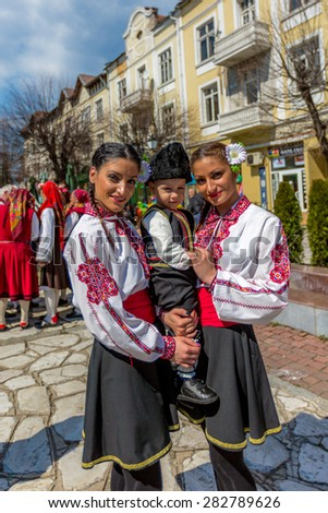 """RAZLOG, BULGARIA - APRIL 13, 2015: Female Bulgarian folklore dancers posing with a small boy during the traditional folklore festival """"1000 national costumes"""" - stock photo"""