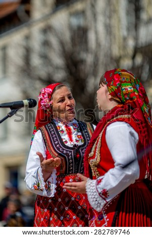 """RAZLOG, BULGARIA - APRIL 13, 2015: Two female Bulgarian folklore singers during the traditional folklore festival """"1000 national costumes"""" - stock photo"""