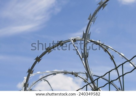 Razor Barbed wire against a blue sky, closeup - stock photo