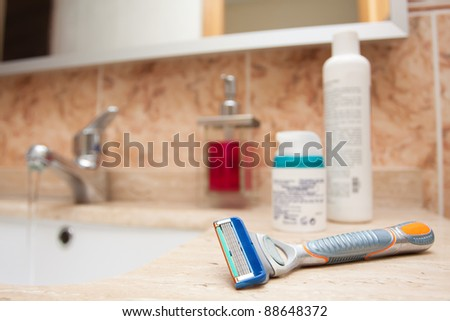Razor blade over a washstand with some cosmetic items in the background blurred.