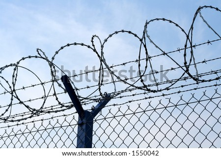 Razor wire atop of a barbed wire secure fence - stock photo