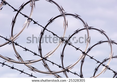 Razor wire fencing against sky - stock photo