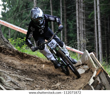 RAZULA, CZECH REPUBLIC - JULY 15: Biker Radomil Stanek rides down his bike at Razula Downhill MTB Cup, July 15, 2012 in Velke Karlovice, Czech republic. - stock photo