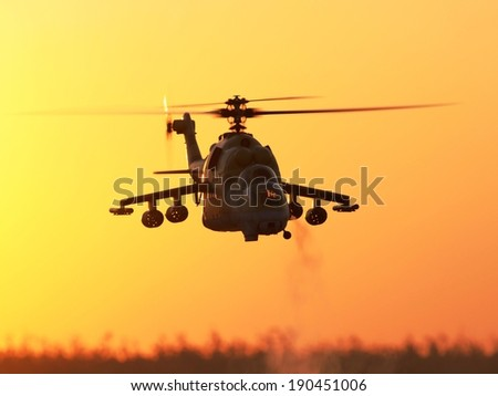 RC Model Hind Scale Helicopter Flying in Flight at Sunset - stock photo