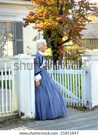 Re-enactment volunteer watches at gate for her returning war hero son or husband.  White wooden fence and sidewalk. - stock photo