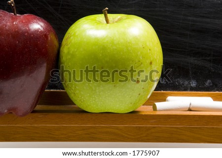 rea and green apple on chalkboard ledge at school - stock photo
