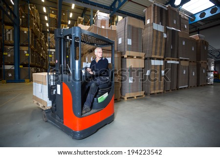 Reach truck driving around the corner in a warehouse where cartboard boxes are stored. - stock photo