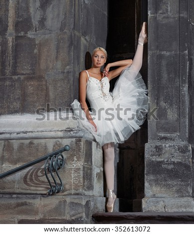 Reaching for dreams. Portrait of a beautiful female ballerina posing near an old castle with her leg raised up against the wall soft focus - stock photo