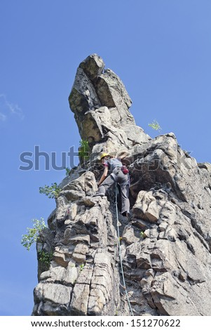 Reaching the top, young woman climbing on a wall, rock climbing in mountains with blue sky. - stock photo