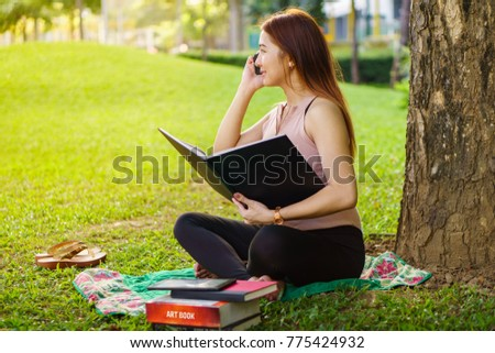 reading a book under the tree while calling