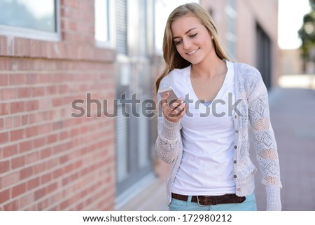Reading a Text Message. Young woman walking while reading a text message.