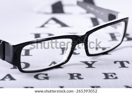 Reading black eyeglasses and eye chart close-up on a light background