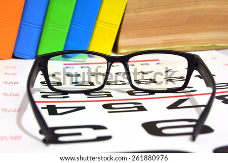 Reading book glasses with eye chart  (shallow DOF) - stock photo