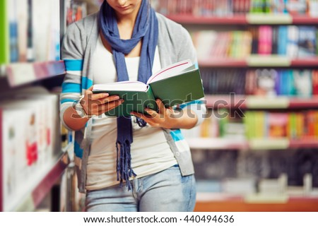 Reading book in library - stock photo