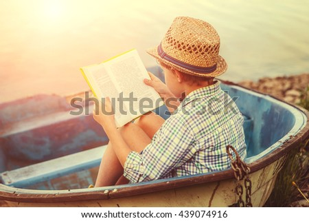 Reading boy in old boat - stock photo
