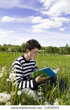 Reading boy sit in a field with a book - stock photo