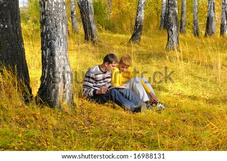 reading boys sit in autumn forest - stock photo