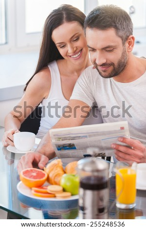 Reading fresh newspaper together. Beautiful young couple bonding to each other and reading newspaper together while sitting in the kitchen and having breakfast - stock photo