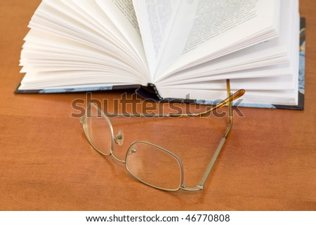 reading glasses and book on the table - stock photo
