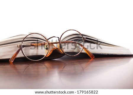 Reading glasses and open book on the table