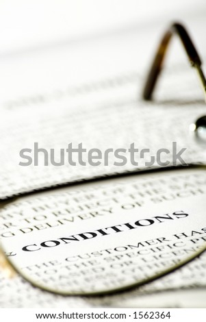 Reading glasses and the word conditions in focus. - stock photo