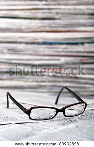 reading glasses lie before a big newspaper pile