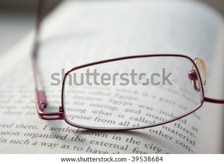 Reading glasses on an open book - stock photo
