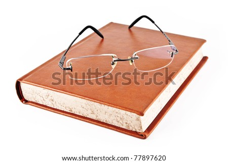 Reading glasses on the book with a brown hard cover, on a white background. - stock photo