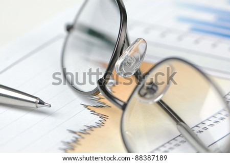 Reading Glasses, Pen and Graphs - stock photo