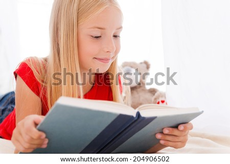 Reading her favorite book. Cute little girl reading book and smiling while lying in bed - stock photo