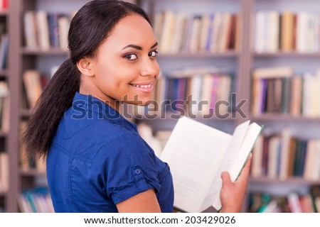 Reading her favorite book. Rear view of beautiful African female student holding a book and looking over shoulder with smile while standing in library - stock photo